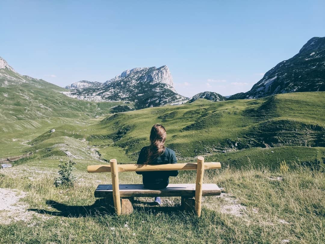 A person sitting on a bench with a mountain in the background