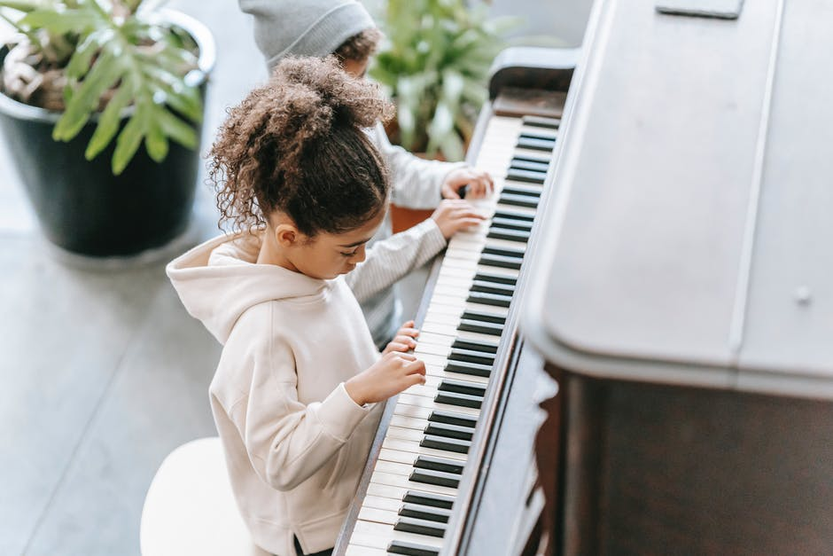 A little boy standing in front of a piano