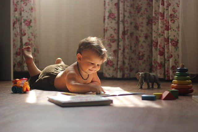 A young boy sitting at a table using a laptop